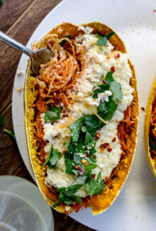fork twirling strands of spaghetti squash in a boat with cheese