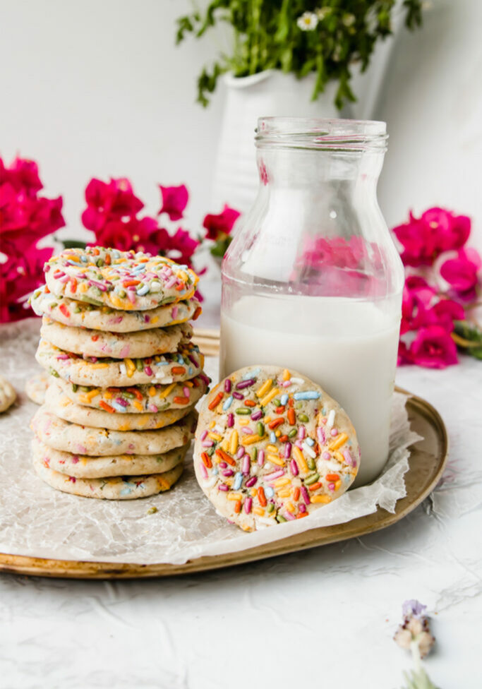 stack of rainbow sprinkle cookies on a tray next to milk
