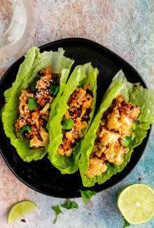 three lettuce wraps filled with sticky sesame cauliflower on a black plate