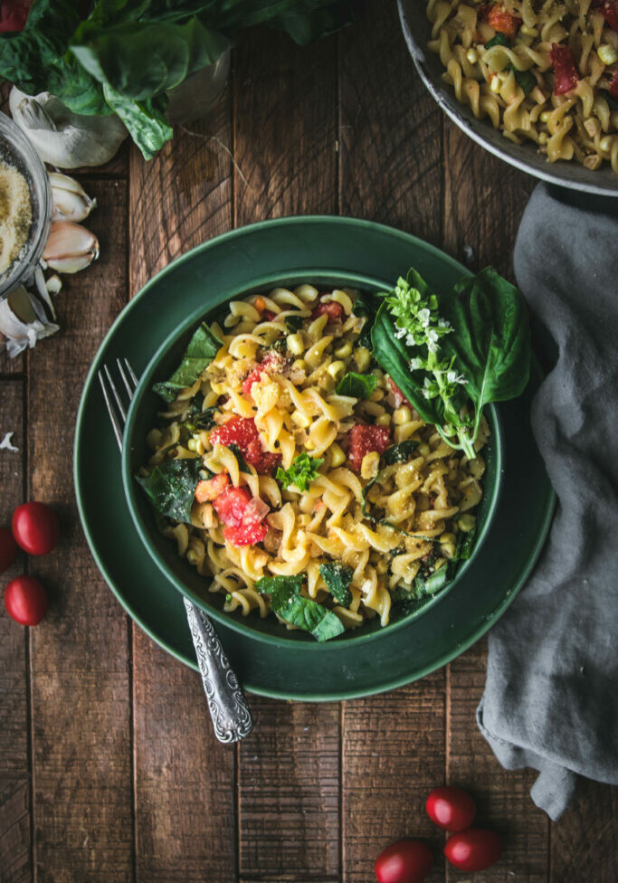 bowl of creamy sweet corn pasta with basil and tomatoes shot from overhead