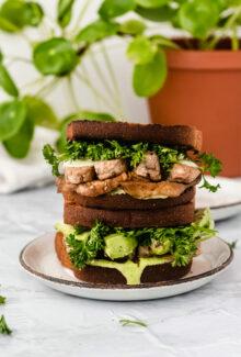 vegan tempeh blt sandwich on a white plate