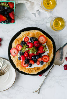 birds eye view of a vegan olive oil cake covered in berries on a black plate
