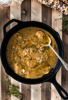 cast iron skillet with vegan gravy with mushrooms on a striped wooden board